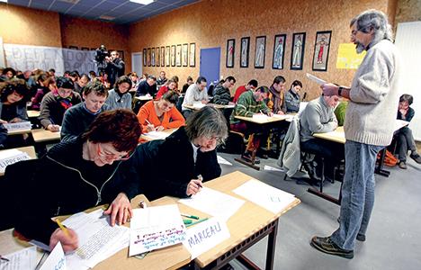 Des parents d'élèves passent eux-mêmes les tests que devront passer leurs enfants, le 17 janvier 2009 dans une école primaire du Mans, pour protester symboliquement contre ces évaluations nationales des élèves de CM2. © Jean-François Monier / AFP