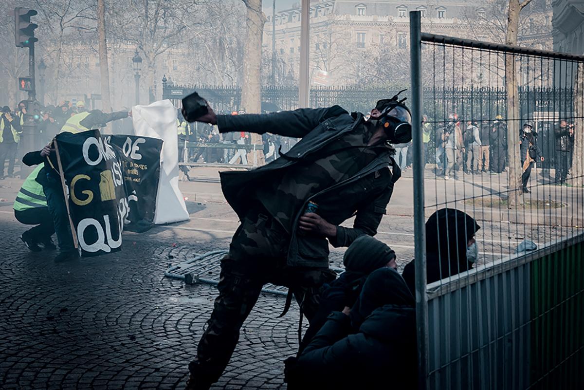 16 mars 2019 aux Champs-Élysées, un manifestant jette une pierre en direction de la police. © Afp forum / Karine Pierre / Hans Lucas